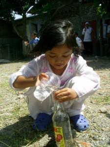 Uli serius menuangkan air gelas ke dalam botol